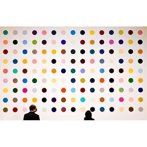 Two people viewing modern art painting of dots