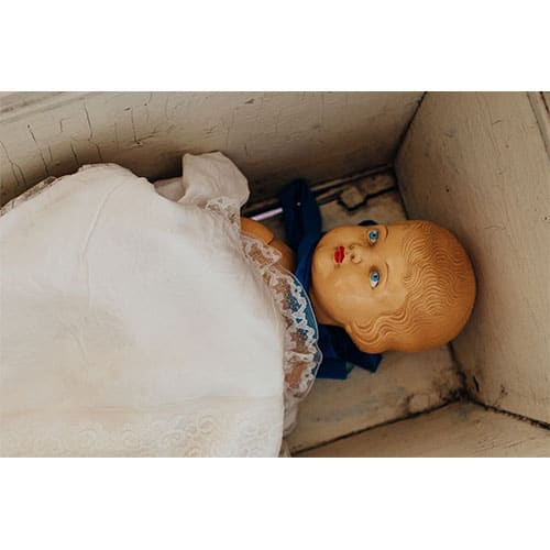 Vintage doll in a box covered with a blanket